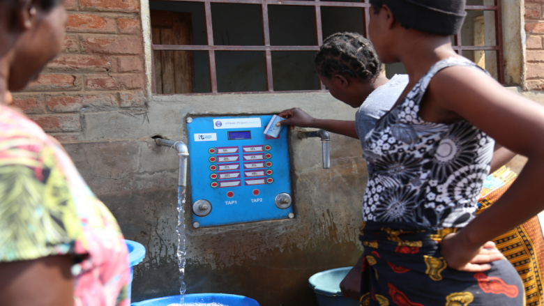 A woman swiping her card to draw water at the e-madzi kiosk in Lilongwe. Credit: Henry Chimbali/World Bank